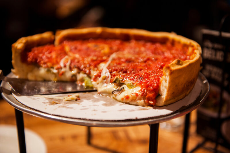 A close up of half of a deep dish pizza pie. A spatula can be seen under the left end of the pizza.