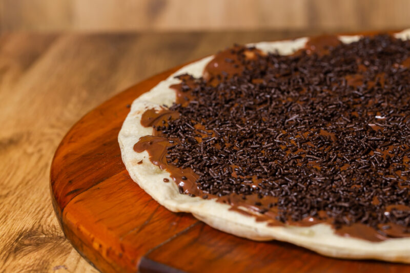 A close up of a chocolate pizza on a wooden surface. The pizza has a chocolate spread with chocolate sprinkles littered on top.