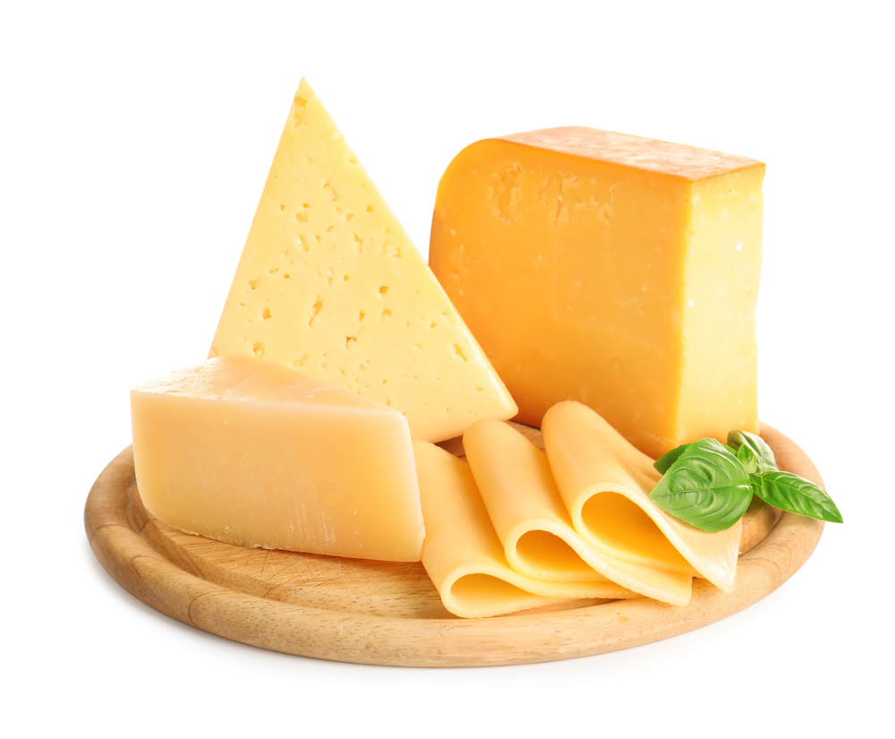 Several different types of cheese are arranged in slices, wedges and blocks on a wooden board with a white background.