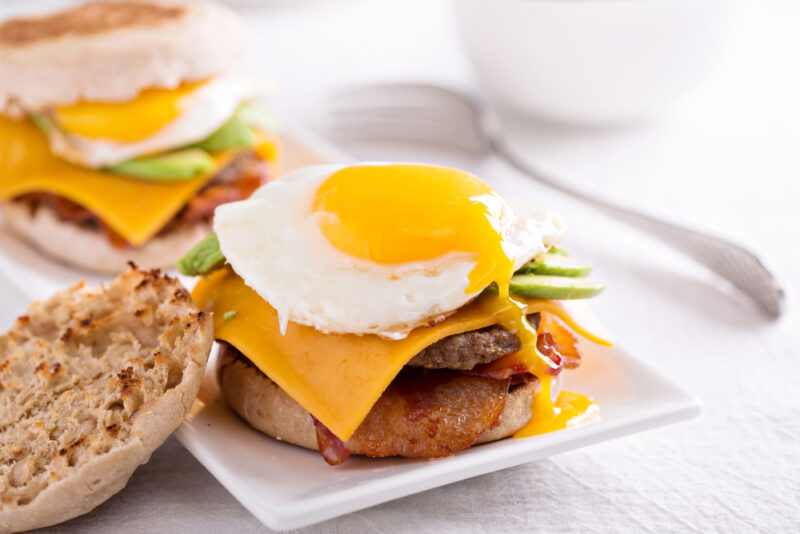 A close up of a breakfast burger on a white, rectangular plate on a tabletop. The burger uses English muffins as buns, and the top one is laid to the side.