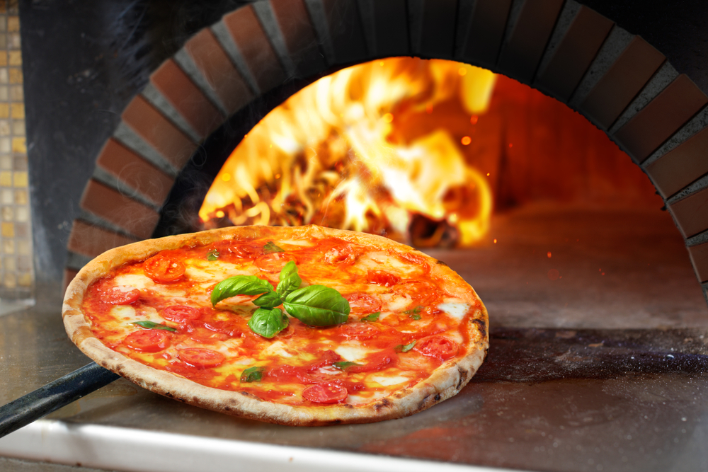 A margherita pizza gets pulled out of a brick oven. The flame from the oven can be seen burning in the background.