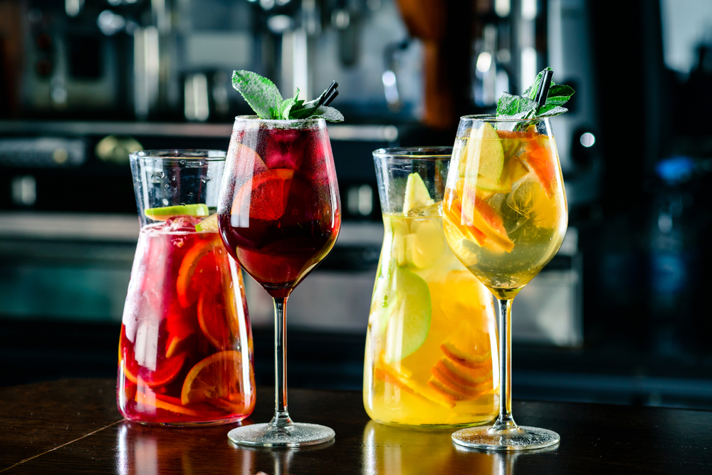 Two pitchers and two wine glasses are set on a table. The left pitcher and glass has red sangria, while the others have white sangria.