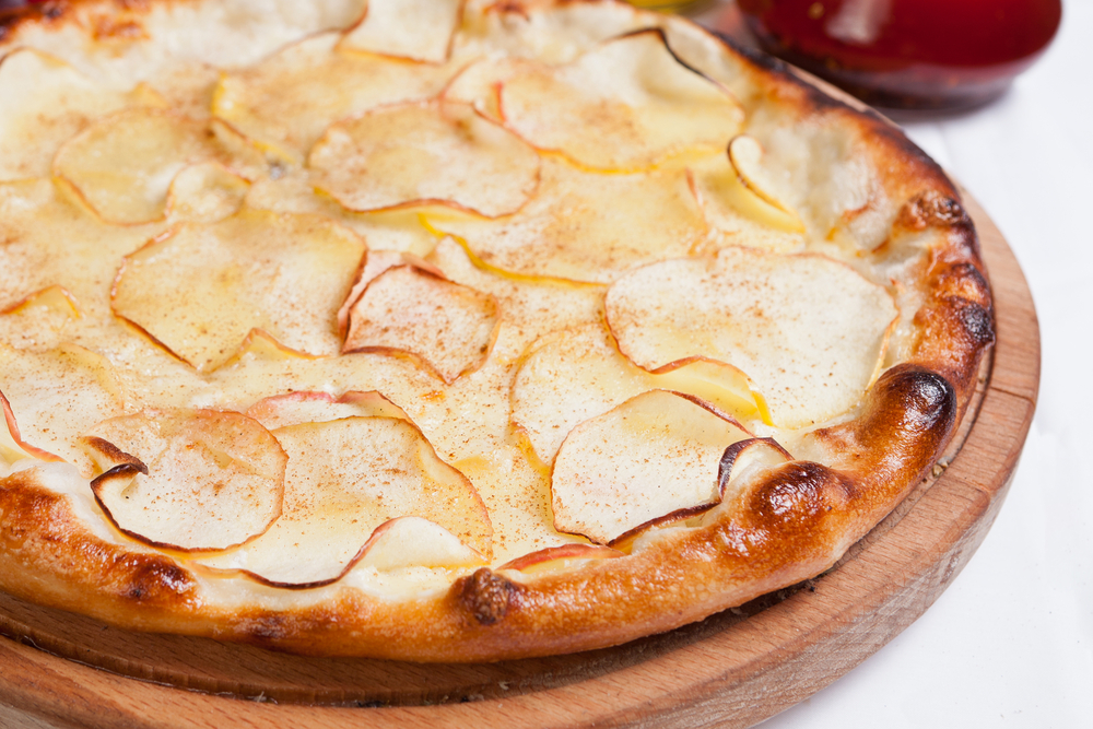 A pizza with several apple slices scattered across the top.